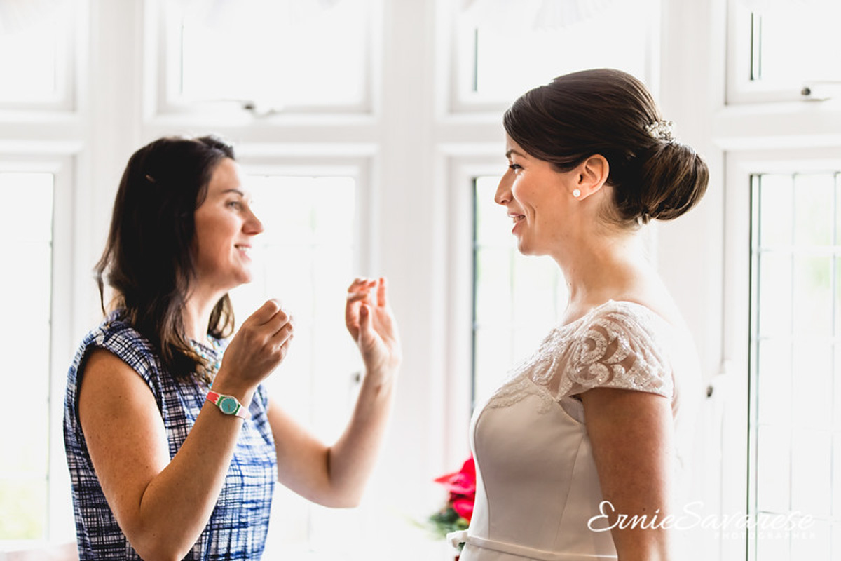 bride with makeup artist on wedding day
